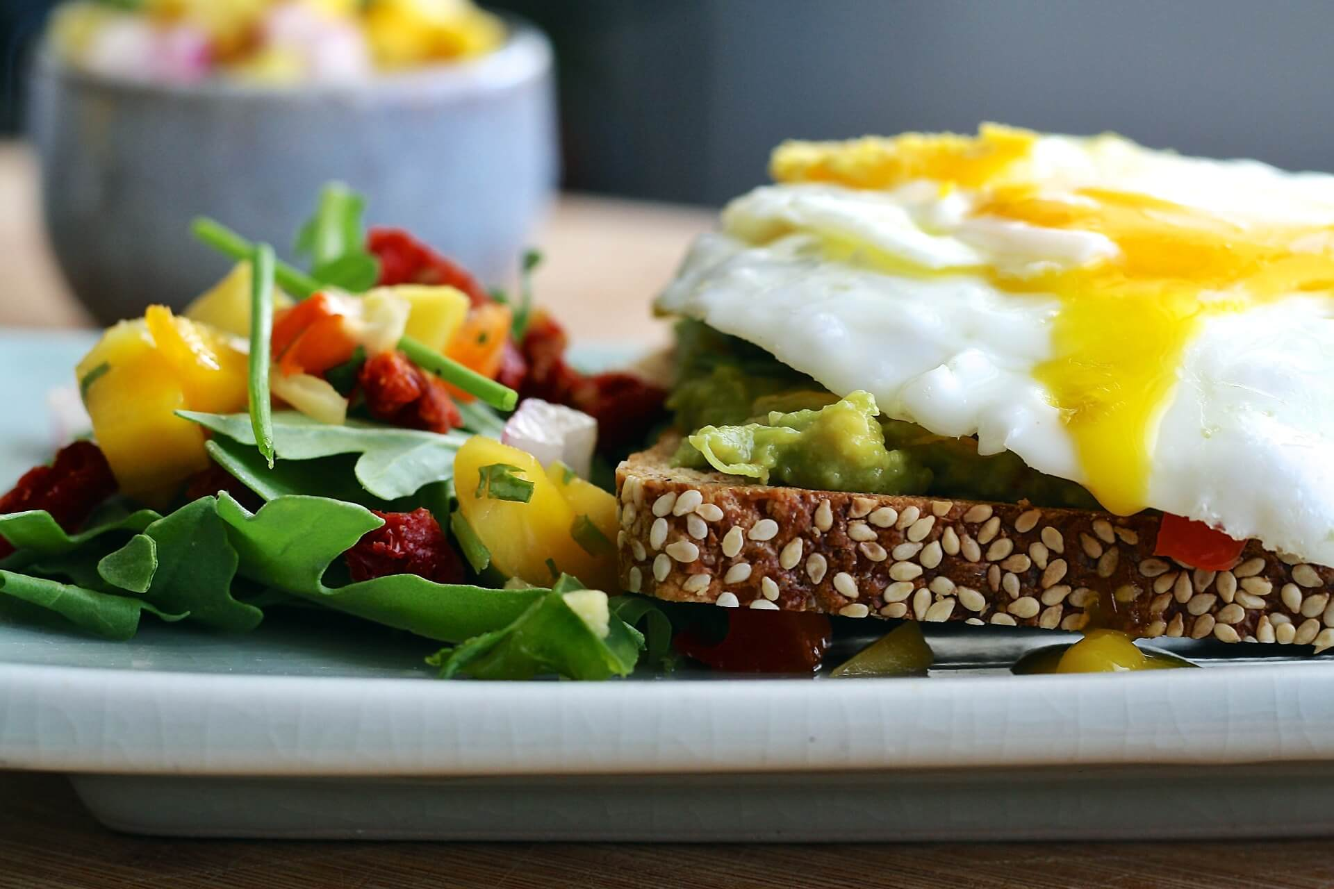 a plate of eggs, greens, and toast