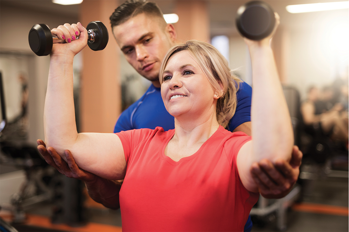Woman doing resistance training with personal trainer