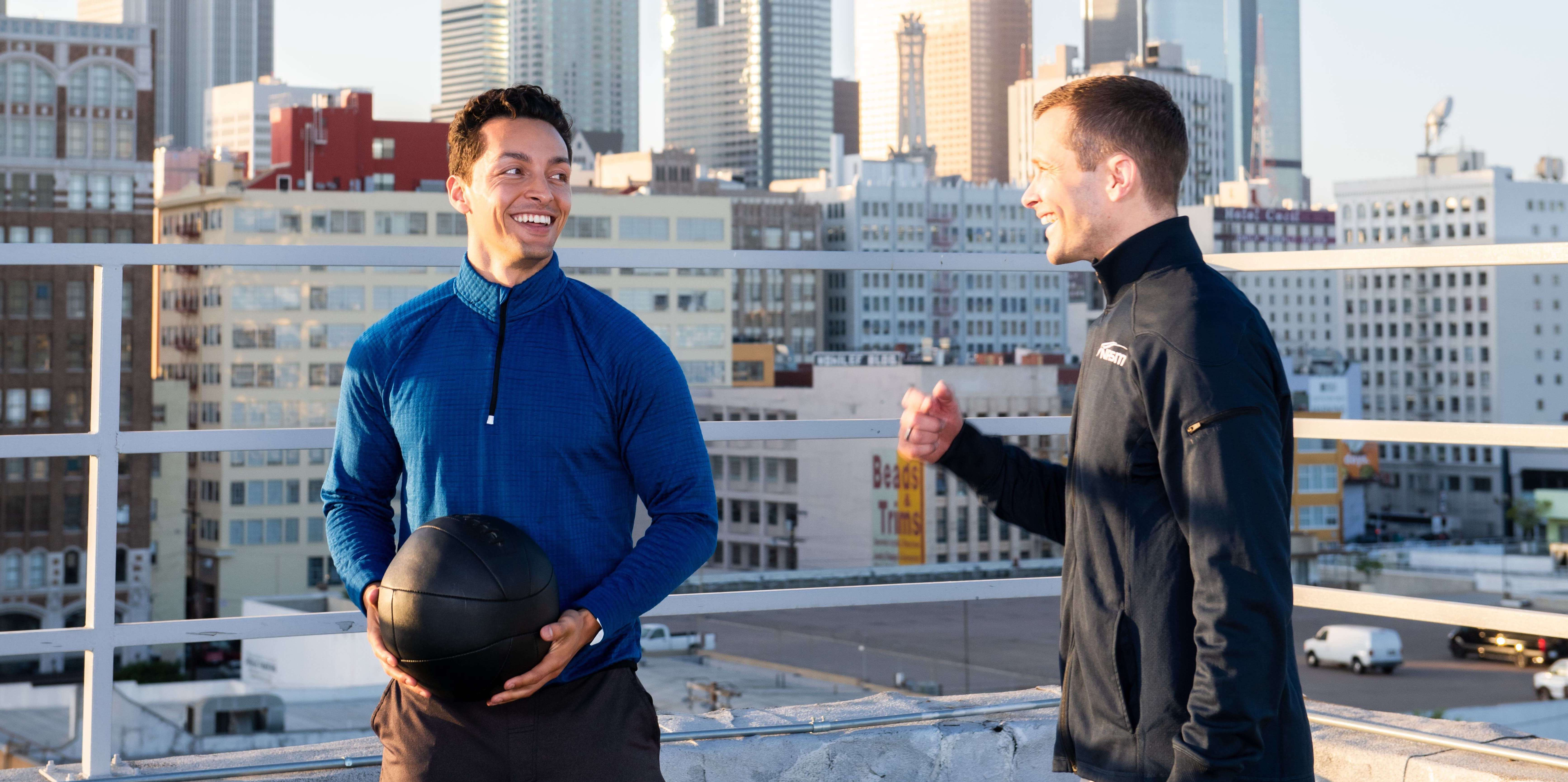 Personal trainer talking to client holding medicine ball